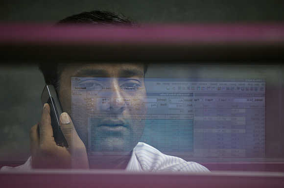 A computer screen is reflected in the glass window of a booth where a broker monitors the market while talking on a mobile phone at the Karachi Stock Exchange.