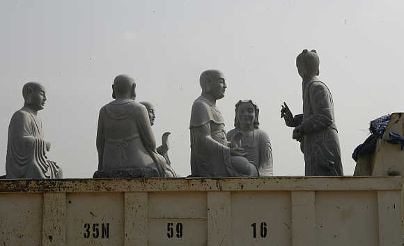 Stone statues of Buddhist arhats sit on a truck at Bai Dinh pagoda in Ninh Binh province, 100km south of Hanoi, Vietnam.