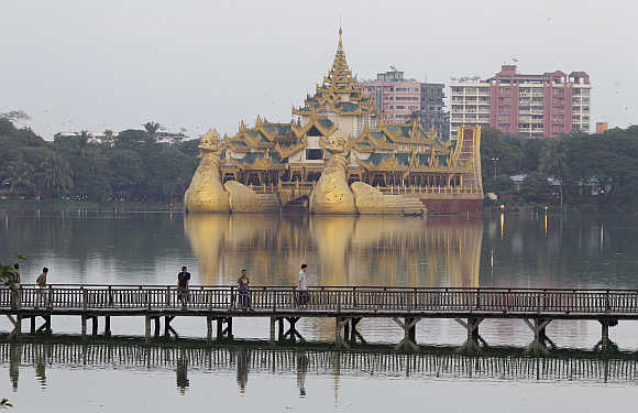 People walk on a wooden bridge in Kandawgyi Lake at Yangon in Burma.