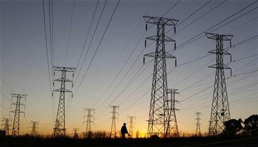 A man walks past electricity pylon.