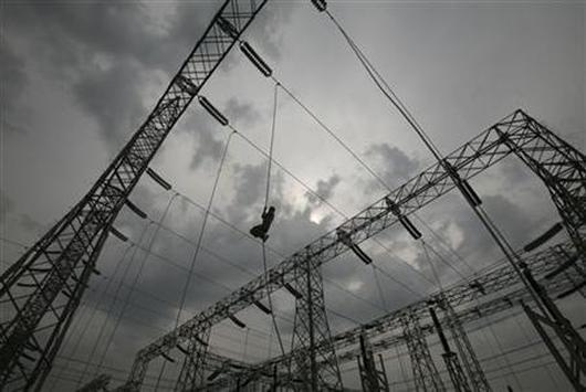 A worker installs an electric power cable on a pylon.