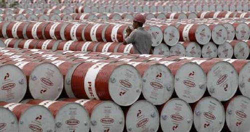 A worker walks in between oil barrels at a depot.