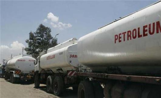 Trucks transporting petrol wait to reload outside a depot.