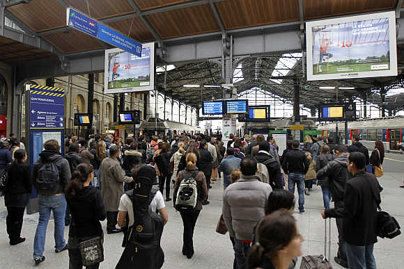 People wait for trains at the Gare Saint Lazare railway station in Paris, France.