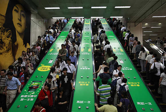 People ride on escalators inside a train station in Taipei, Taiwan.
