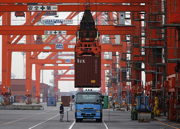 Workers load a container on a truck at a port in Tokyo, Japan.