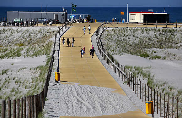 People walk along sand dunes at the Gravenzande coast with the Rotterdam Europort as a backdrop in the Netherlands.