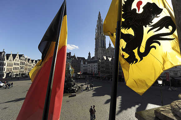 Belgian, left, and Flemish flag, right, are seen at the town square in Antwerp, Belgium.