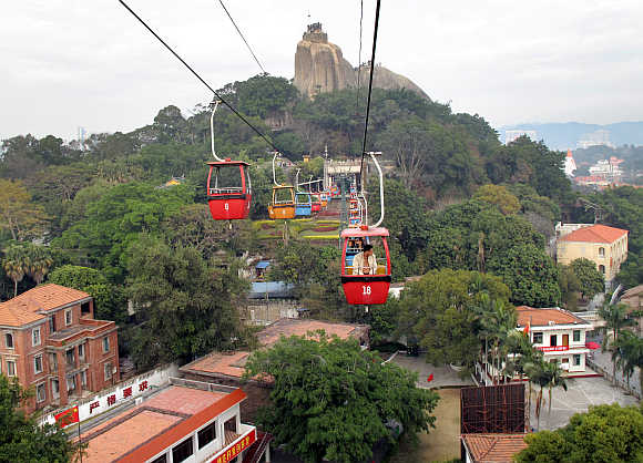 A tourist rides a cable car above old buildings in the southeastern Chinese city of Xiamen.