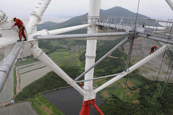 Labourers work on the Damaoshan power transmission tower in Zhoushan, Zhejiang province, China.
