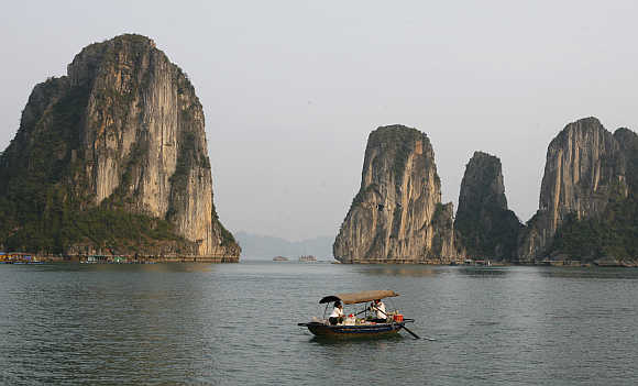 Residents ride in a bamboo boat in Ha Long Bay, 150km from Hanoi, Vietnam.