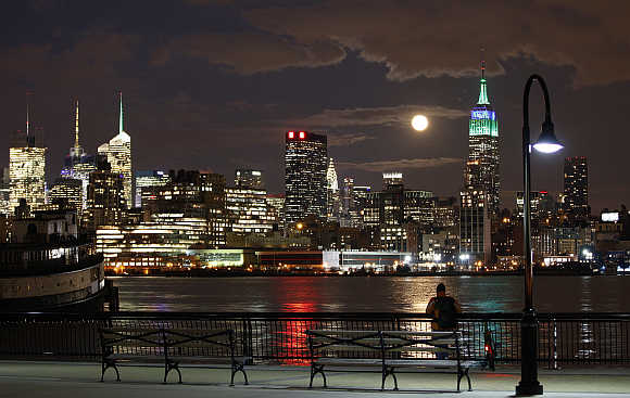 A full moon rises behind the Empire State Building in New York as a man watches along the Hudson River in Hoboken, New Jersey, United States.