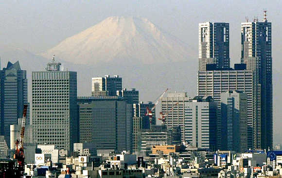 Mt Fuji looms over skyscrapers in Tokyo's Shinjuku district, Japan.