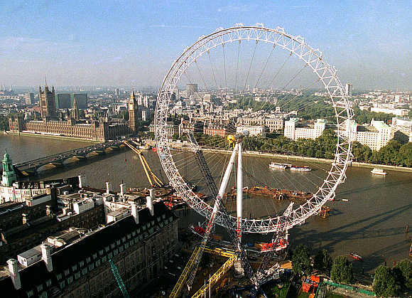 London Eye, a giant ferris wheel, dominates the South Bank of the River Thames as it towers above Big Ben and the Houses of Parliament.