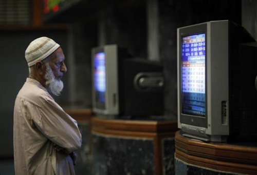 A Pakistani monitors stock prices at the Karachi Stock Exchange.