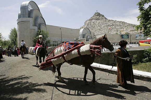 A horse carries a folded-up yurt, a traditional felt tent, as they head to a handicraft fair in Osh, 700km south of the capital Bishkek, in Kyrgyzstan.