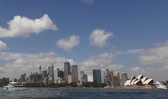 A catamaran leaves the central business district, with the Sydney Opera House in the background, in Australia.