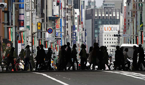 Pedestrians cross a street at Tokyo's Ginza shopping district in Japan.