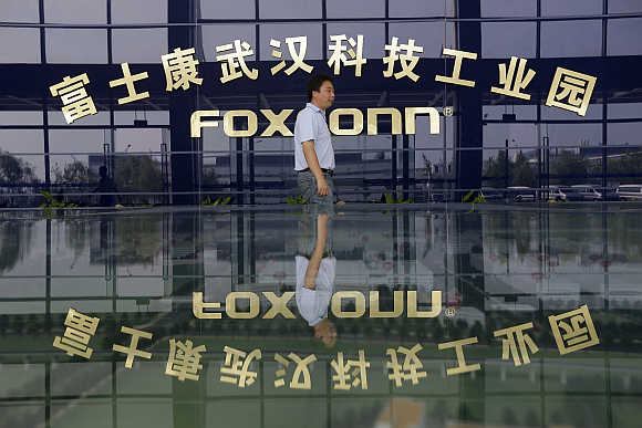 A man walks past a logo of a Foxconn factory in Wuhan, Hubei province, China.