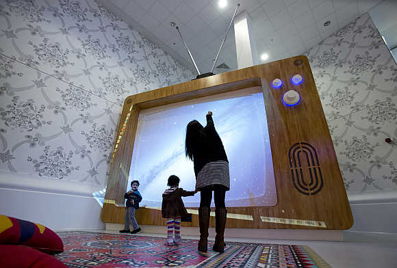 A woman and young children interact with a giant television set at the Ann Riches Healing Space for young patients at the Royal London Hospital in London, United Kingdom.