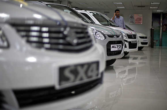 A sales executive speaks on his mobile phone as he stands in between Maruti Suzuki cars inside a showroom in New Delhi.