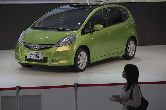 A woman walks past a Honda Fit Hybrid car in Guangzhou, China.