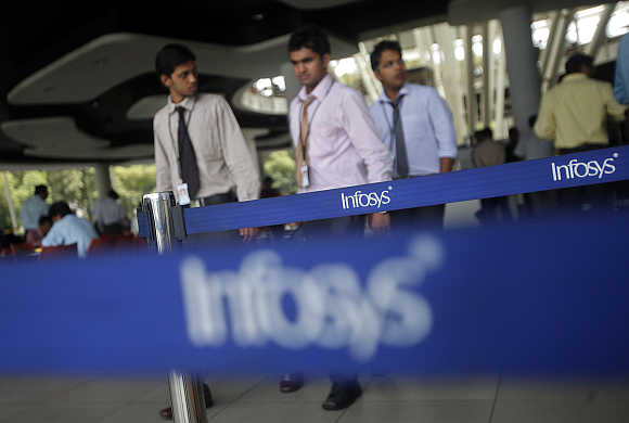 Employees of Infosys walk past Infosys logos at their campus in the Electronic City area in Bangalore.
