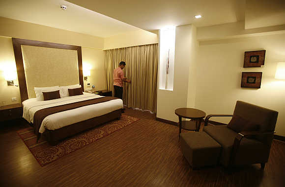 An employee prepares a room for guests at the Four Points hotel in Ahmedabad.