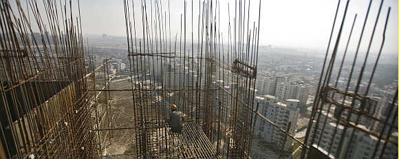 A labourer works at the construction site of a residential complex at Noida.