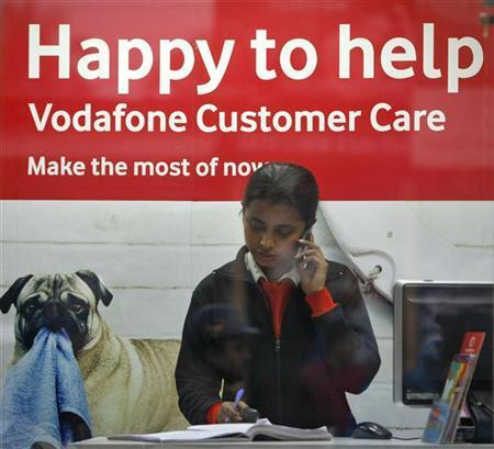An employee talks on mobile phone inside a Vodafone store.