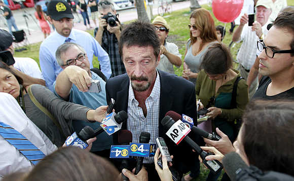 Computer software pioneer John McAfee speaks with reporters outside his hotel in Miami Beach, Florida.