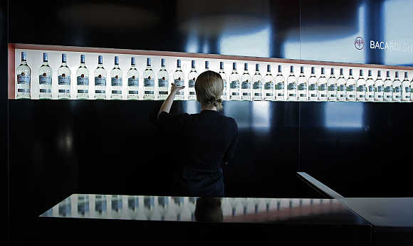 An exhibitor arranges Bacardi rum bottles in Cannes, southeastern France.