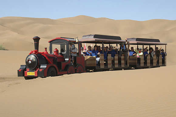 Tourists wave as they travel around the Kumtag Desert by a sightseeing train at a scenic spot in Turpan, northwest China's Xinjiang Uygur Autonomous Region.