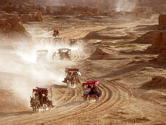 Tourists in donkey-drawn carriages visit the ancient city of Gaochang, Turpan, northwest China's Xinjiang Uygur Autonomous Region.