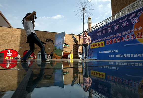 Tourists take pictures outside the Xinjiang International Bazaar, a major trading complex, in Urumqi, capital of northwest China's Xinjiang Uygur Autonomous Region.