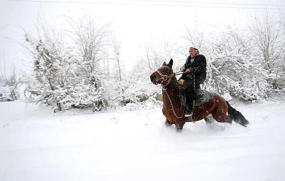 An ethnic Uighur man rides a horse in snow in Yili, Xinjiang Uighur Autonomous Region.