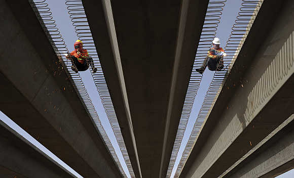 Labourers work on building a highway to connect Kashgar and Aksu by the end of October 2013 in Aksu, Xinjiang Uighur Autonomous Region.