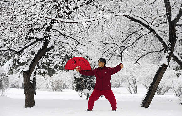 A woman practices tai chi with a fan after a snowfall in Shenyang, Liaoning province.