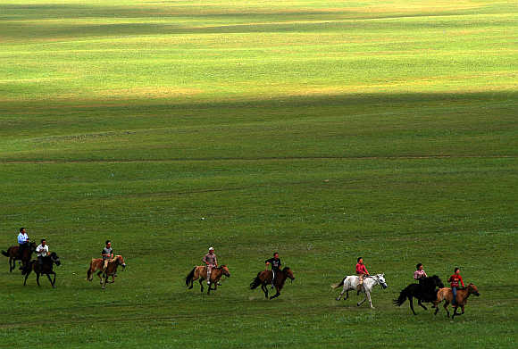 Nomads participate in a horse race on the Kerqin Grassland in Inner Mongolia.
