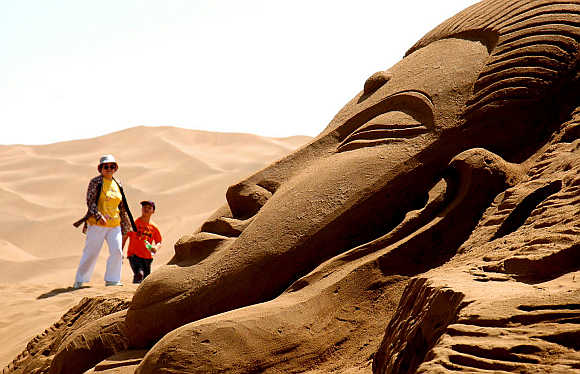 Two tourists look at a sand sculpture in a desert in Turpan in Xinjiang Uygur Autonomous Region.