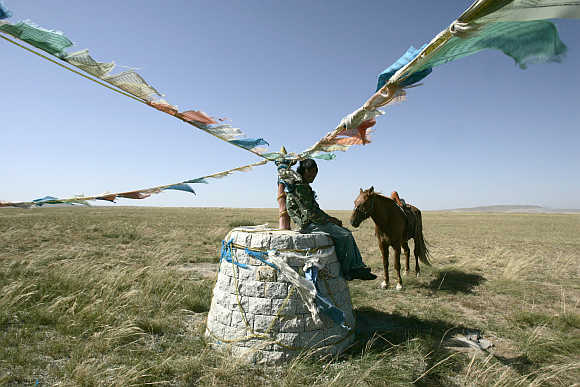 A shepherd rests in a pasture in Xilinhot in Inner Mongolia.