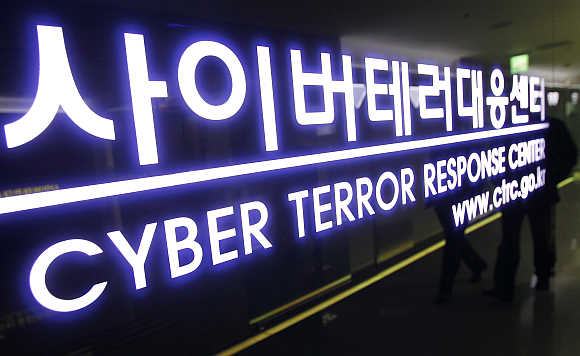 Police officers of the Cyber Terror Response Centre are reflected as they walk out of their office at the headquarters of the National Police Agency in Seoul, South Korea.