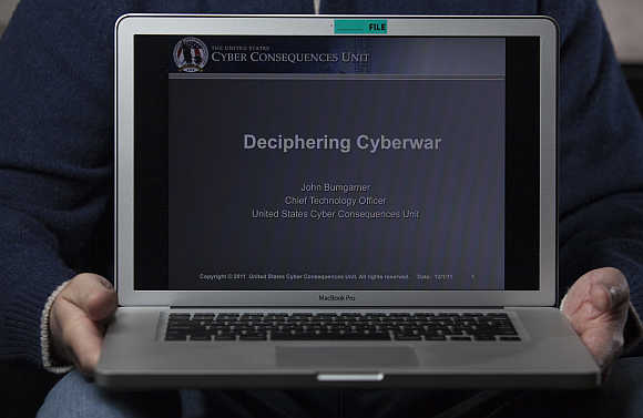 John Bumgarner, a cyber warfare expert who is chief technology officer of the US Cyber Consequences Unit, a non-profit group that studies the impact of cyber threats, holds a notebook computer while posing for a portrait in Charlotte, North Carolina, United States.