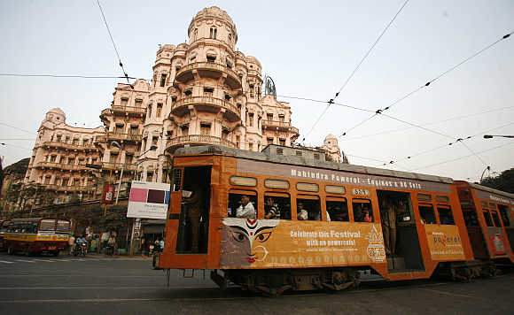 A tram passes beside a heritage building in Kolkata.