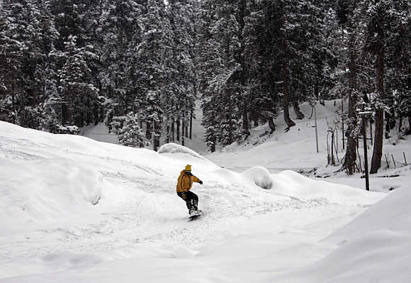 A man snow boards down a slope in Gulmarg, 55km west of Srinagar.