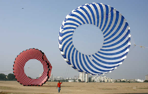 A kite-flying enthusiast tightens the strings of a 30 feet in diameter kite in Ahmedabad.