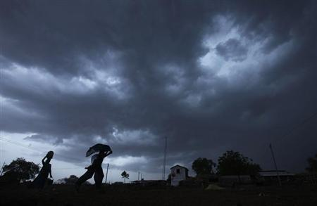 A girl runs for cover as it rains as monsoon clouds gather over Meerwada village in Guna district in Madhya Pradesh.