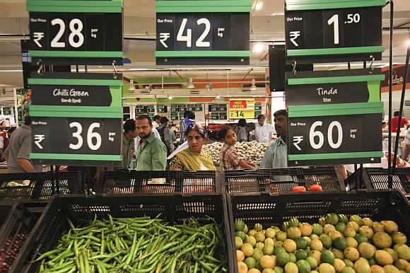 Prices for various vegetables are displayed as people shop in the fresh foods section of a Reliance Fresh supermarket in Mumbai.