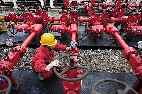 A worker performs a routine check to the valves at a natural gas appraisal well of Sinopec in Langzhong county, Sichuan province, China.