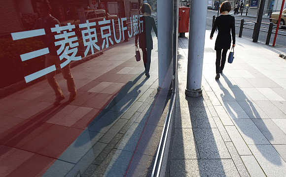 A pedestrian walks past a signboard of a branch bank of Mitsubishi UFJ Financial Group in Tokyo.
